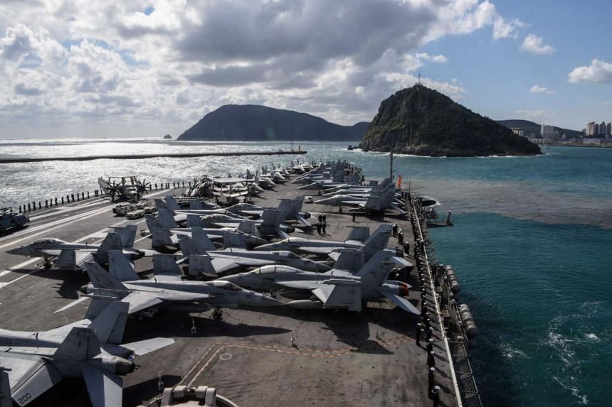 The four-day joint exercise in the western Pacific involves three flattops - USS Ronald Reagan, USS Nimitz and USS Theodore Roosevelt - and seven South Korean warships including three destroyers.