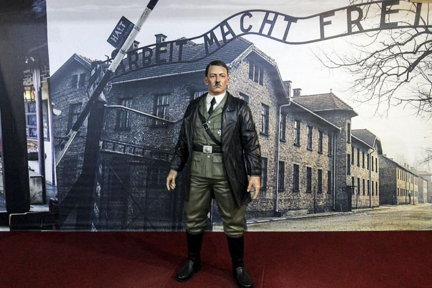 A wax statue of Adolf Hitler is displayed in front of a picture of the Auschwitz-Birkenau concentration camp, at the De ARCA Statue Art Museum in Yogyakarta, Indonesia.