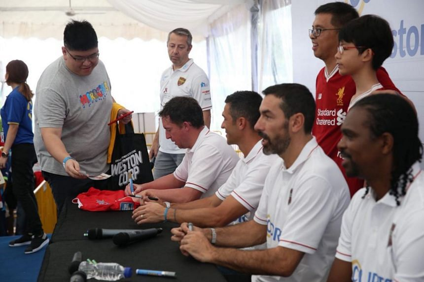 The Straits Times reader Josiah Tan gets autographs signed by (from centre-right) Robbie Fowler, Luis Garcia, Robert Pires and Nwankwo Kanu.