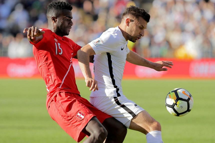 New Zealand's Kosta Barbarouses competes for the ball with Christian Ramos of Peru during the match.