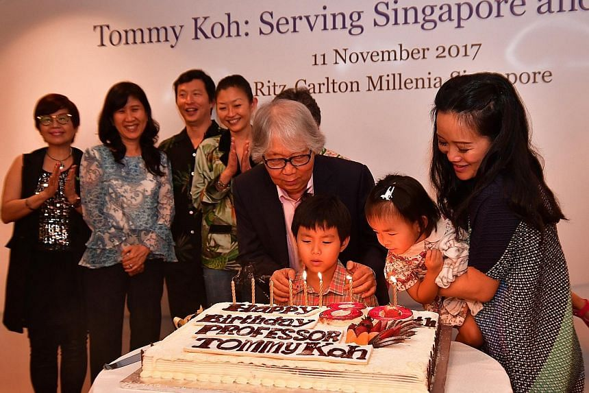 Professor Tommy Koh blowing the candles with his grandchildren Toby Koh and Tara Koh, and daughter-in-law Tan Su-lyn. In the background are his son Wei Koh (third from left) and other members of his family.