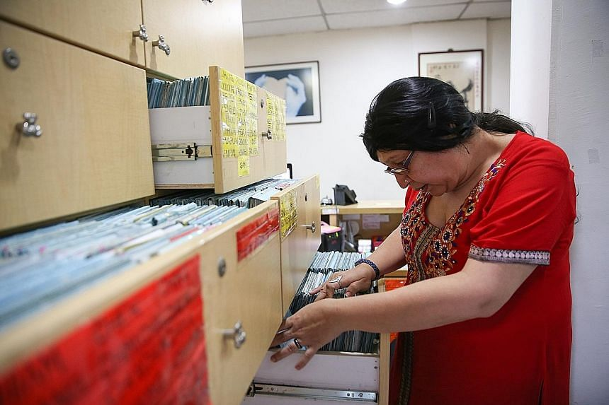 """Clinic assistant Devi Bhattacharjee, 51, combing through Dr Lee's patient records. They are held in more than 10 groaning drawers - each the size of a microwave oven. Said Dr Lee: """"Every year, our drawers get heavier and every few years, we have to u"""