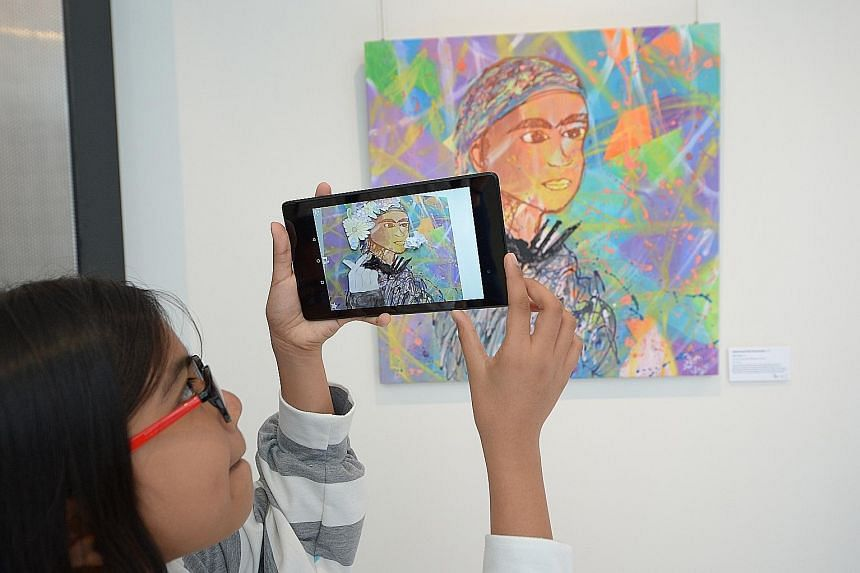 """The Little Arts Academy student Nashariyah Shamsudin, 11, showing off her work Fun Vines, which includes an element of """"augmented reality"""", at the centre's Northpoint City campus launch yesterday. The academy provides free arts training for beneficia"""