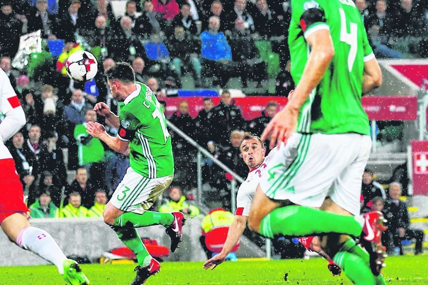 A shot by Switzerland's Xherdan Shaqiri hits Northern Ireland's Corry Evans on Thursday, leading to a contentious penalty for handball.