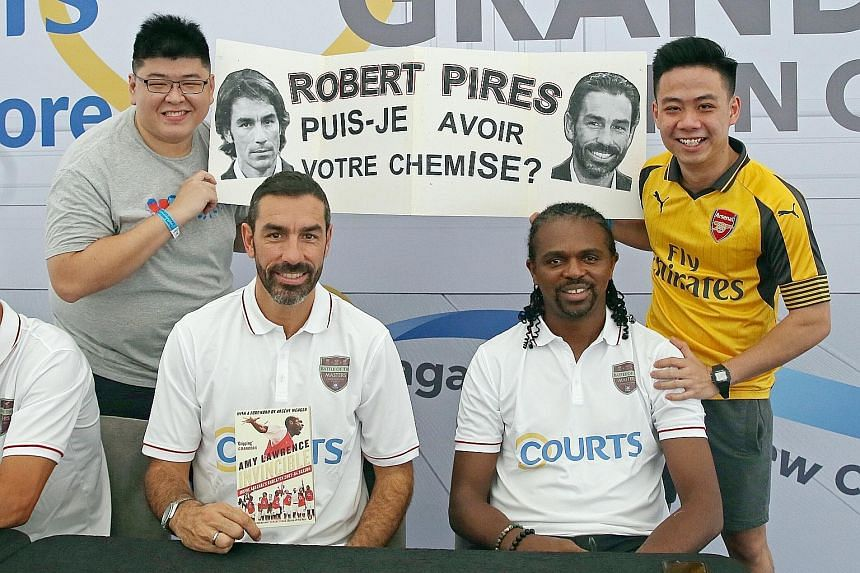 Josiah Tan (left) and Zheng Xuan, hold up a sign askingRobert Pires (third from right) for his shirt at the Courts Megastore yesterday