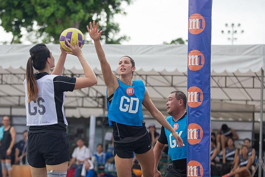 New Zealand Silver Ferns' Kayla Cullen defending a shot by Singapore goal shooter Yu Meiling, as M1 chief innovation officer Alex Tan awaits a rebound, during a charity exhibition game at the M1 Corporate Netball Challenge. Yesterday's event saw 35 t