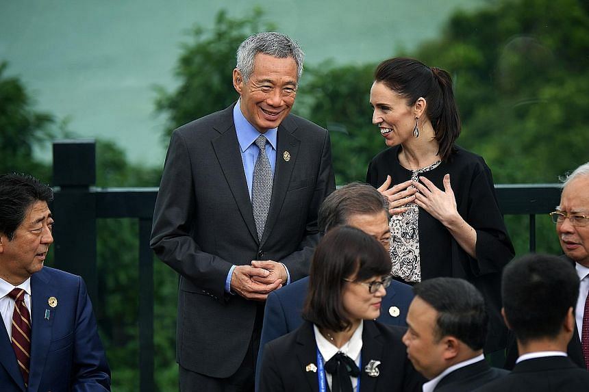 PM Lee Hsien Loong and New Zealand PM Jacinda Ardern at a group photo for leaders yesterday. With them are (from left) Japanese PM Shinzo Abe, South Korean President Moon Jae In (partly hidden) and Malaysian PM Najib Razak.