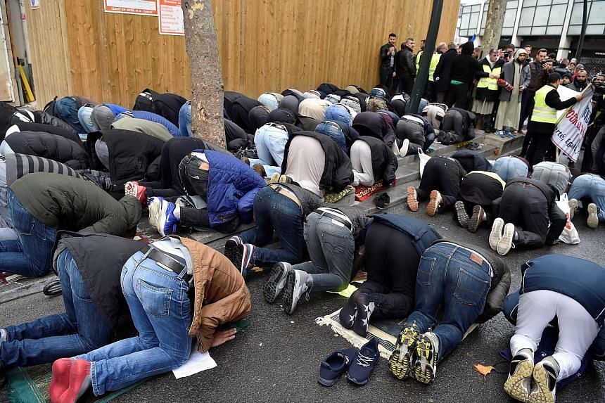 Muslims praying in a street in Clichy, near Paris, last Friday, while city mayor Remi Muzeau and other political leaders protest against the public worship. Lawmakers are calling for a ban on what they see as an unacceptable use of public space, whil
