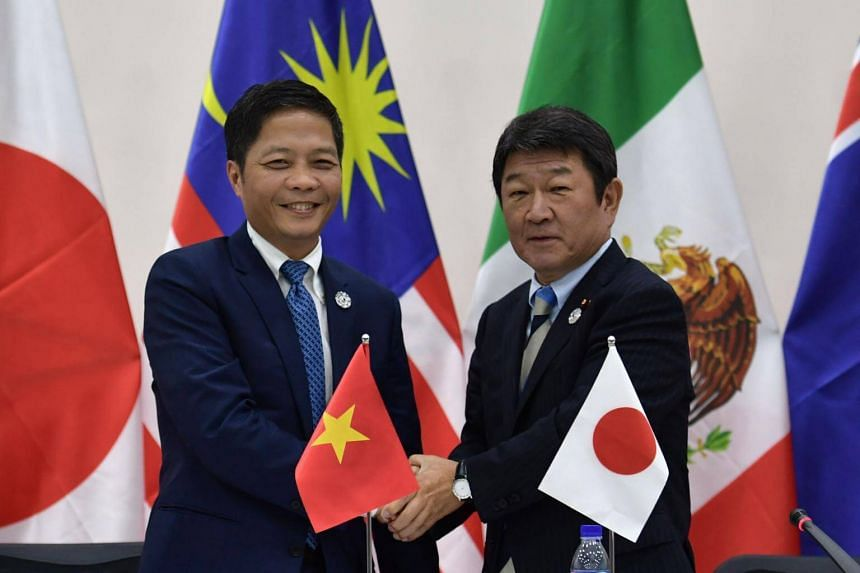 Vietnam's Trade Minister Tran Tuan Anh (left) shakes hands with Japan's Economic Revitalisation Minister Toshimitsu Motegi at the end of a Trans Pacific Partnership (TPP) press conference in Danang on Nov 11, 2017.