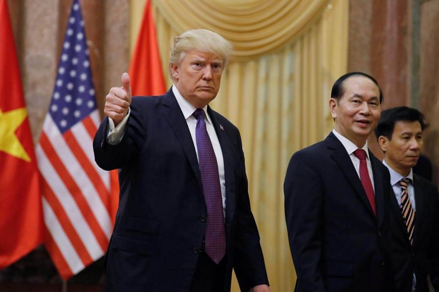 US President Donald Trump gives a thumbs up next to Vietnam's President Tran Dai Quang upon his arrival at the Presidential Palace in Hanoi, Vietnam.