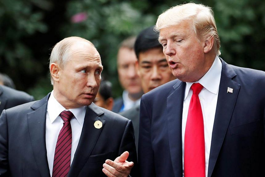 US President Donald Trump and Russia's President Vladimir Putin talk during the family photo session at the APEC Summit in Danang, Vietnam.
