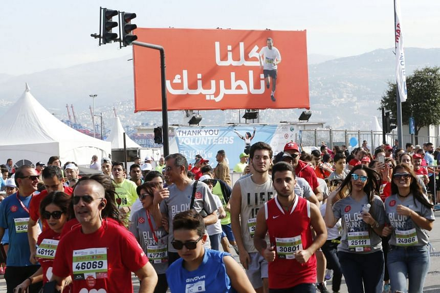 Participants running past a billboard bearing the picture of former PM Saad Hariri, during the Beirut marathon on Nov 12, 2017.
