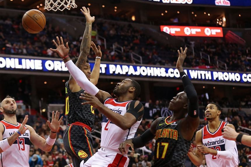 Washington Wizards guard John Wall (centre) going for a layup against Atlanta Hawks forward John Collins (left) and guard Dennis Schroder (right) during their NBA game on Nov 11, 2017.