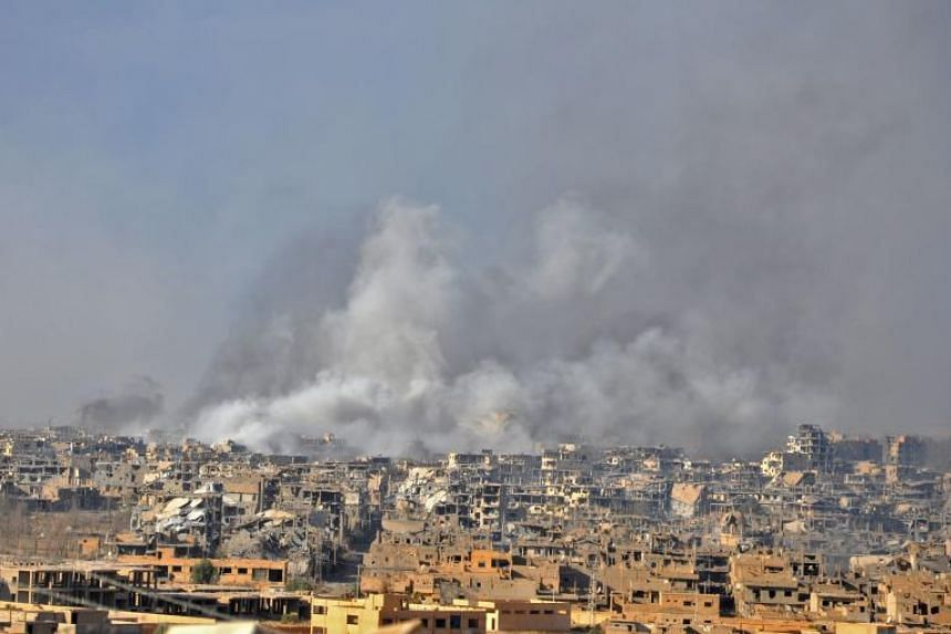 Smoke rising from buildings following an air strike by Syrian government forces in the eastern city of Deir Ezzor, on Oct 31, 2017, during an operation against ISIS group militants.