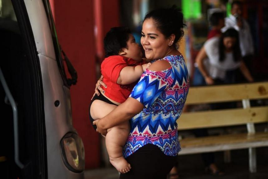Isabel Pantoja, 24, holds her ten-month-old baby Luis Gonzales as they wait at the bus station in Colima city where they are headed for Luis' medical check-upon Nov 9, 2017.
