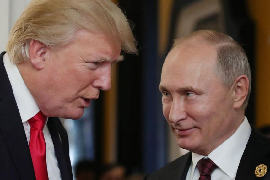 US President Donald Trump  chats with Russia's President Vladimir Putin as they attend the Apec Economic Leaders' Meeting, part of the Apec leaders' summit in the central Vietnamese city of Danang on Nov 11, 2017.