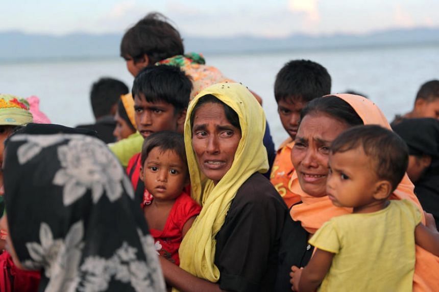 Rohingya refugee women cry while crossing the Naf River with an improvised raft to reach to Bangladesh in Teknaf, Bangladesh, Nov 12, 2017. PHOTO: REUTERS