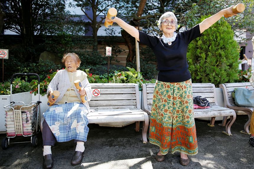 Elderly Japanese citizens working out with wooden dumb-bells during a health promotion event in Tokyo in September.