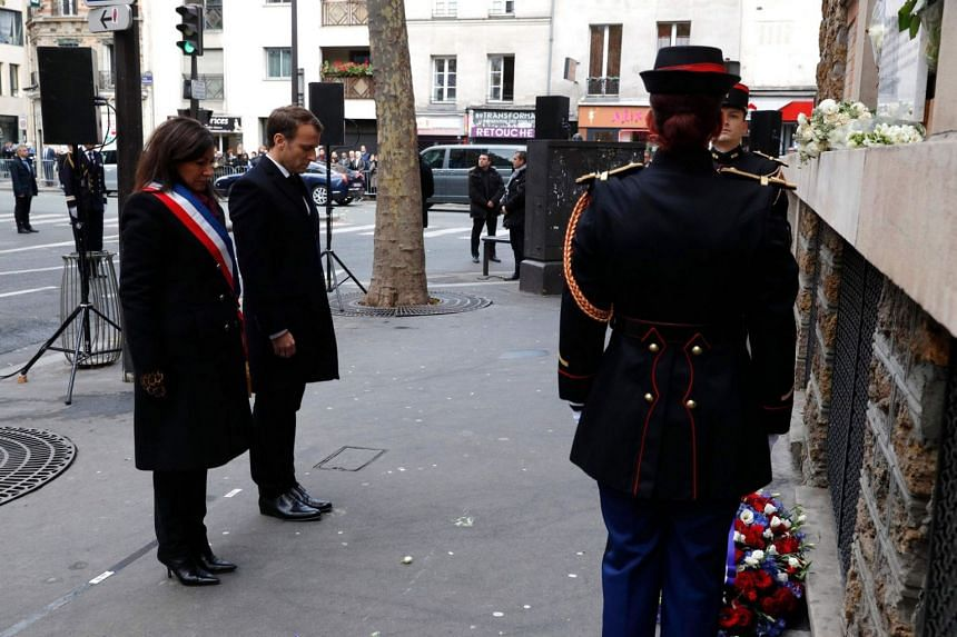 French President Emmanuel Macron and Paris Mayor Anne Hidalgo attend a minute of silence after they laid a wreath of flowers in front of a commemorative plaque at La Belle Equipe bar and restaurant.