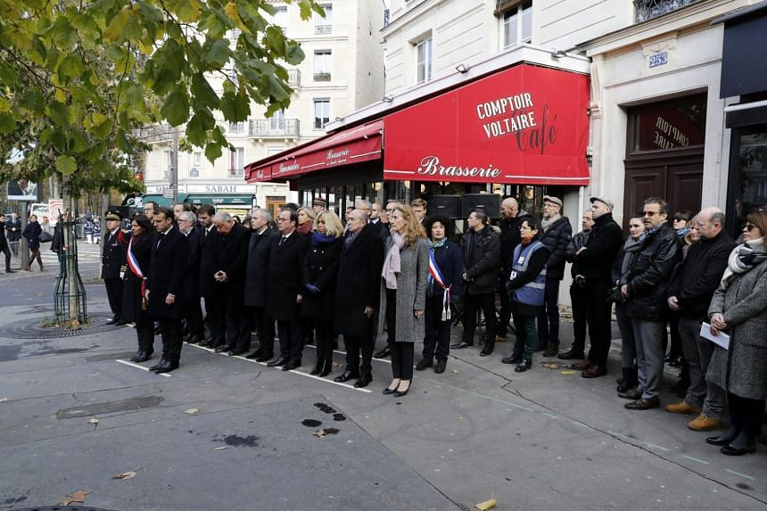 French President Emmanuel Macron (third from left) and Mayor of Paris Anne Hidalgo (second from left) stand in front of Comptoir Voltaire bar during a ceremony marking the second anniversary of the Paris attacks on Nov 13, 2017.