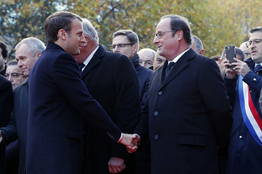 French President Emmanuel Macron (left) shakes hands with former French President Francois Hollande (right) as they stand in front of a commemorative plaque outside the Stade de France stadium, in Saint-Denis, near Paris.