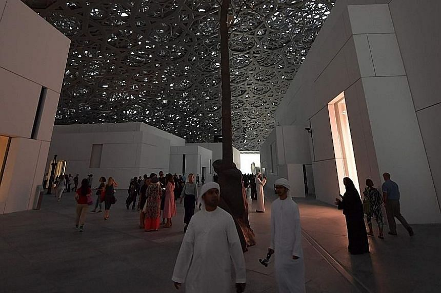 Visitors walk past a piece of art titled Germination by Italian artist Giuseppe Penone at Louvre Abu Dhabi.
