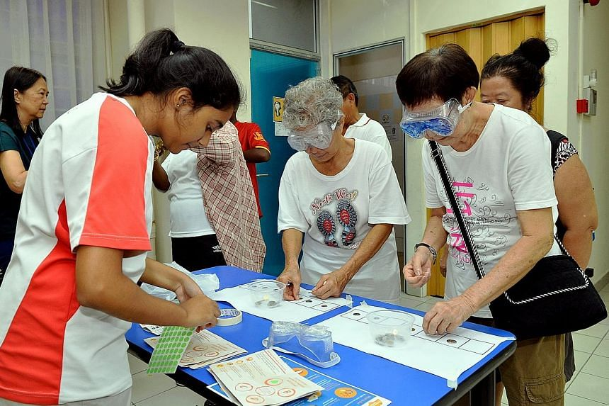 """At the """"Walk With Me: Our Journey Of Remembering"""" event in Nee Soon South yesterday, about 100 participants performed daily tasks such as buttoning a shirt and sorting coins while wearing gloves or goggles. The idea was to give them a sense of the ch"""