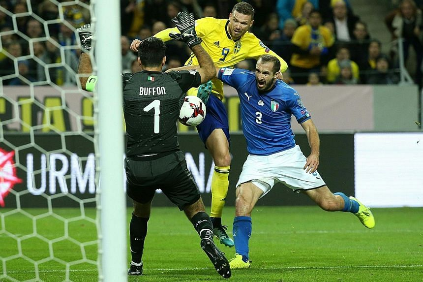 Sweden forward Marcus Berg challenging Italian defender Giorgio Chiellini for the ball as Italy goalkeeper Gianluigi Buffon looks to thwart his advances. The Italians have to overturn a one-goal deficit to reach a tournament they last won in 2006.