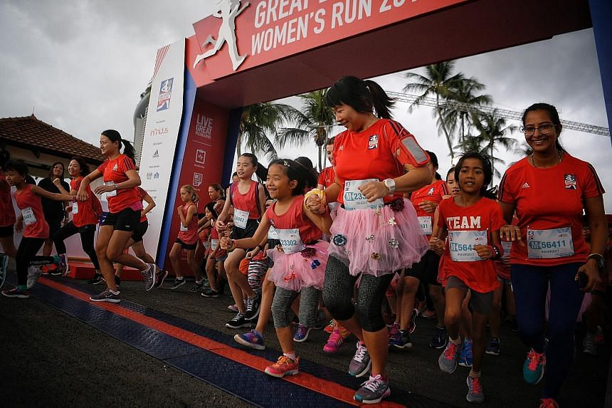 Left: Mother-and-daughter pairs leaving the starting point during the new Mummy + Me 2km category at the Great Eastern Women's Run. Below: Jin Mingming raising her arms as she crosses the finish line for the half marathon in first place. The professi