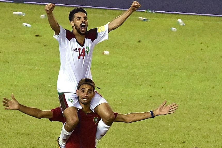 Morocco's Mbark Boussoufa getting a piggyback ride for his part in helping his country reach the World Cup Finals. Morocco's 2-0 win over the Ivory Coast sealed their spot while ruling their opponents out of next year's showpiece event in Russia.