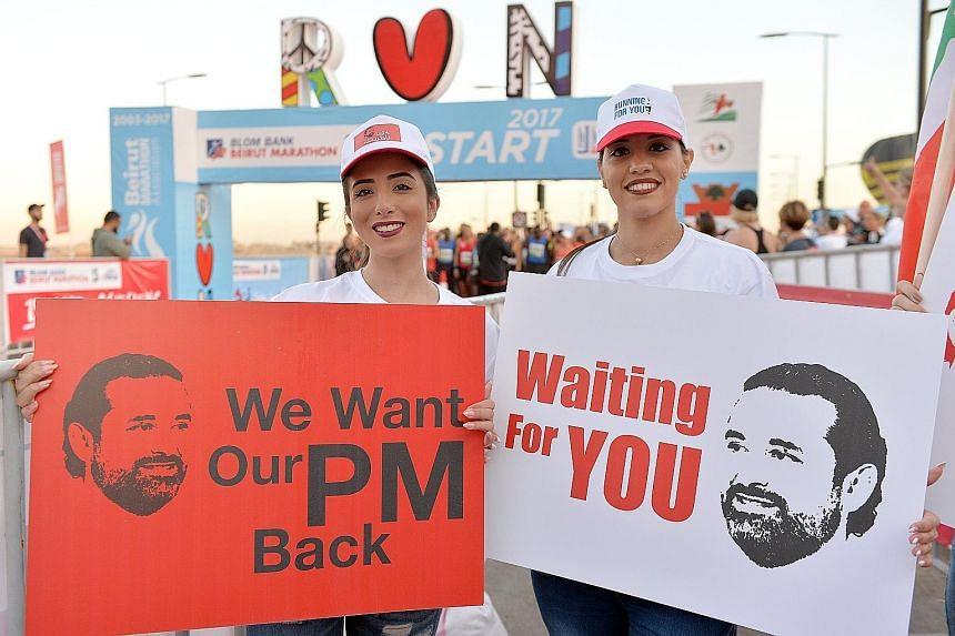 Lebanese women with placards demanding the return of their prime minister, Mr Saad al-Hariri, from Saudi Arabia, during the annual Beirut International Marathon in Lebanon yesterday. Lebanon's president has told ambassadors that Saudi Arabia kidnappe