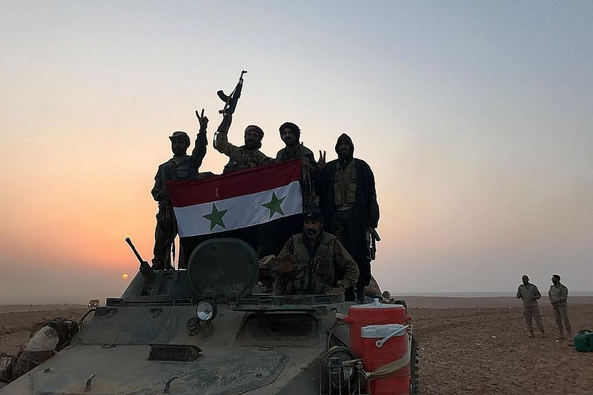 Syrian forces displaying the national flag in the village of Suway'iah, near Albu Kamal, last Friday. Syrian regime forces and allied militia from Lebanon, Iraq and Iran overran Albu Kamal last Thursday but lost the town again just two days later aft
