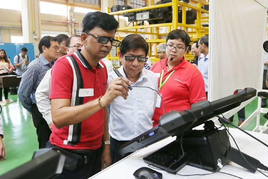 Mr Anand (left), a technical officer, explains the virtual reality training solutions to Transport Minister Khaw Boon Wan at Tuas West Depot on Nov 13, 2017.