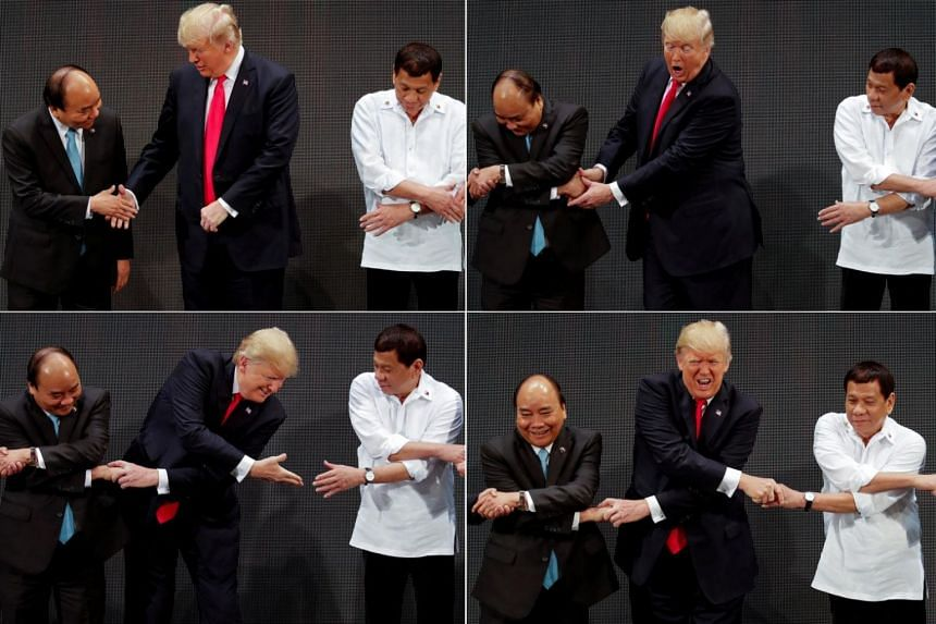 In a combination photo, US President Donald Trump expresses surprise as he attempts the traditional Asean handshake as he participates in the opening ceremony of the Asean Summit in Manila, Philippines on Nov 13, 2017.
