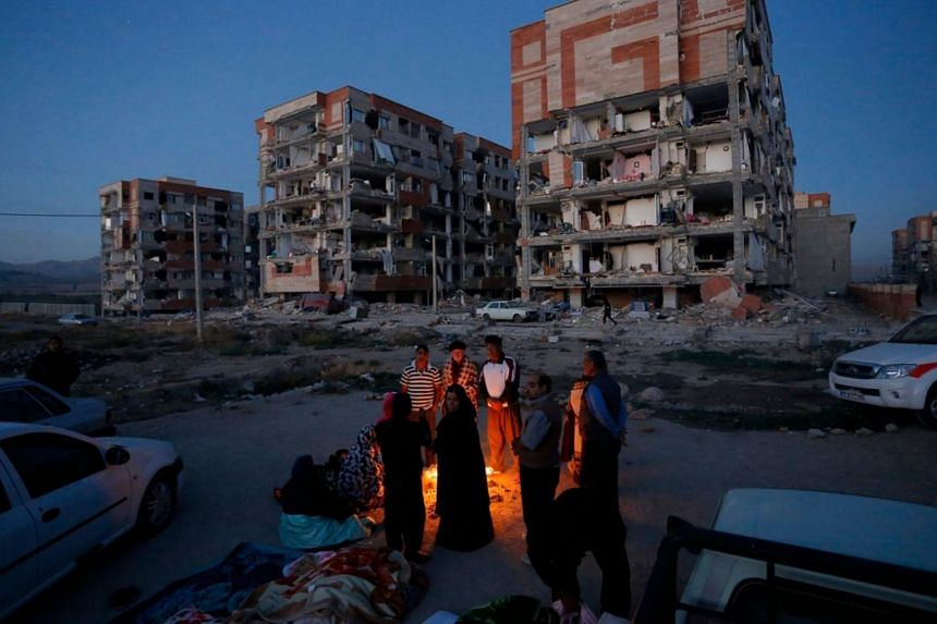 Residents huddle by a fire in an open area following a 7.3-magnitude earthquake at Sarpol-e Zahab in Iran's Kermanshah province on Nov 13, 2017.