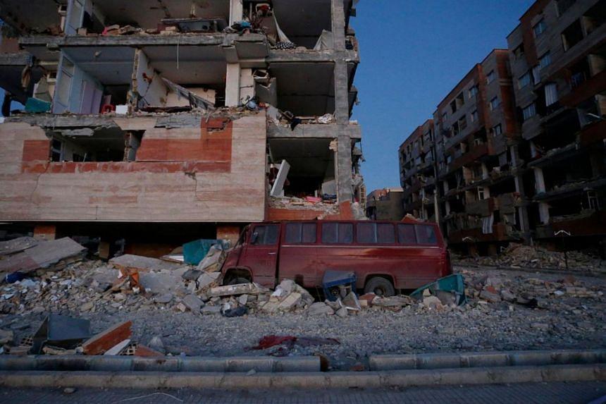 A damaged van and buildings are seen following a 7.3-magnitude earthquake at Sarpol-e Zahab in Iran's Kermanshah province on Nov 13, 2017.