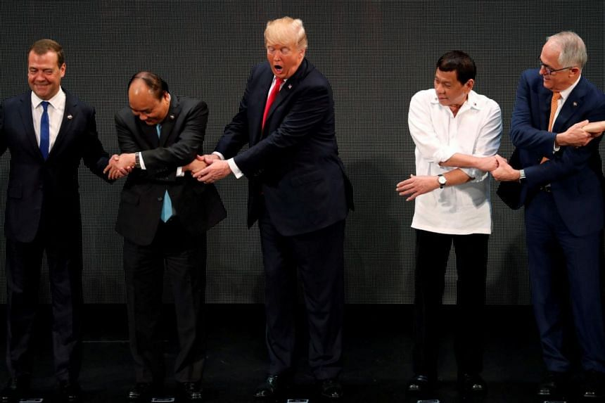 US President Donald Trump registers his surprise as he realises other leaders, including Russia's Prime Minister Dmitry Medvedev, Vietnam's Prime Minister Nguyen Xuan Phuc, President of the Philippines Rodrigo Duterte and Australia's Prime Minister M
