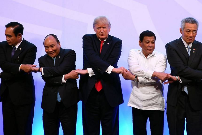 "US President Donald Trump (centre) had told a gathering of Pacific Rim leaders the US would no longer tolerate ""chronic trade abuses"" from the region."