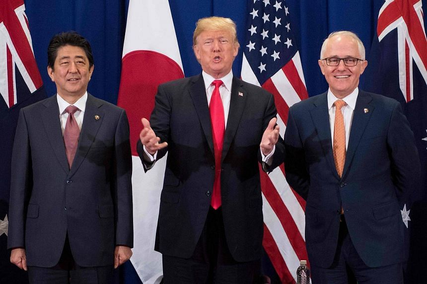 On the sidelines of a summit of East and South-east Asian leaders in Manila, US President Donald Trump (centre) met Japan's Shinzo Abe (left) and Australia's Malcolm Turnbull (right).