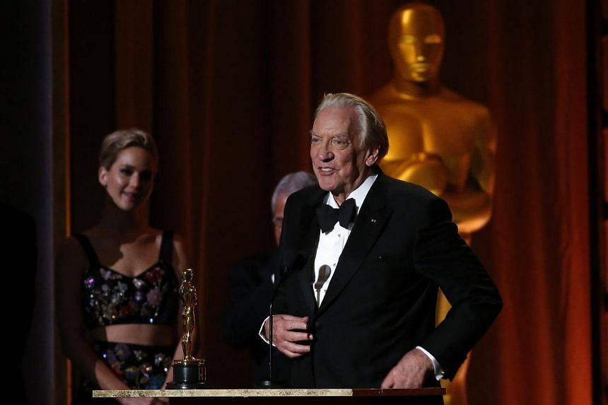 Actor Donald Sutherland accepts the Governors Award as presenter Jennifer Lawrence looks on.
