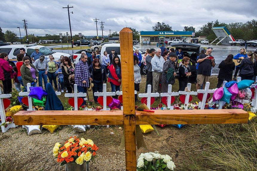 People gather in front of crosses at First Baptist Church in Sutherland Springs, Texas, which has been transformed into a memorial to honor those who died.