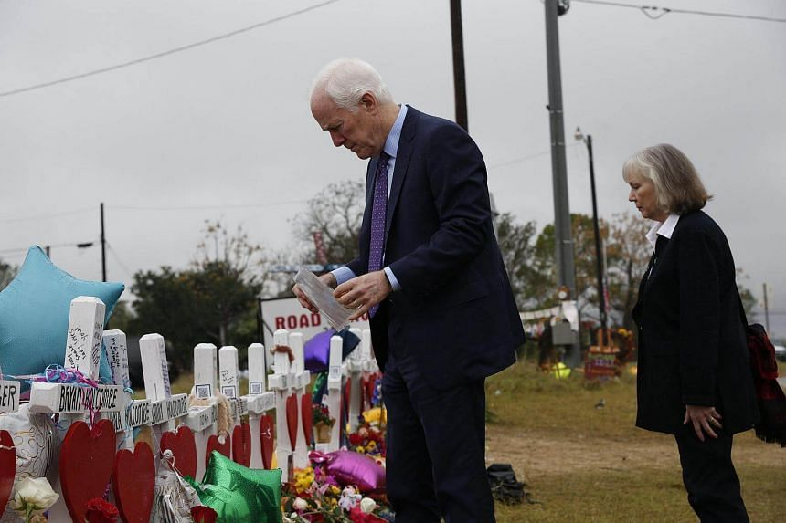 Texas Senator John Cornyn and his wife Sandy Cornyn look over a family photo after leaving a flag at Sutherland Springs' First Baptist Church in Texas.