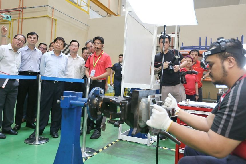 (From left) LTA deputy chief executive for infrastructure and development Chua Chong Kheng, LTA chief executive Ngien Hoon Ping and Minister Khaw Boon Wan watch a technician working on Augmented Reality Guided Training Solutions at Tuas West Depot on