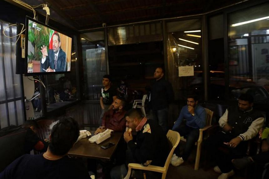 People watch an interview with Lebanon's resigned prime minister Saad Hariri at a coffee shop in Beirut on Nov 12, 2017.
