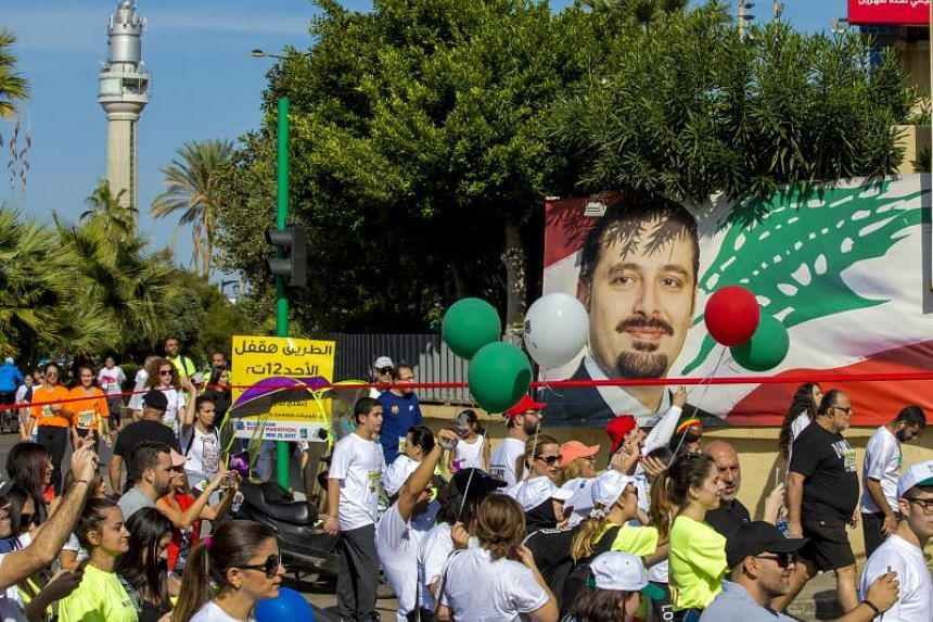 Participants pass by a billboard bearing a portrait of Lebanon's prime minister Saad Hariri with Arabic words reading 'We are all with you' as they take part in the eight kilometers race during the annual Beirut International Marathon, Beirut, Lebano
