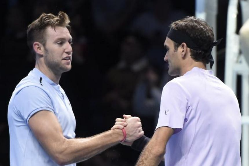 Roger Federer (right) of Switzerland celebrates winning against Jack Sock of the USA during their Men's singles Round Robin match at the ATP World Tour Finals tennis tournament at the O2 Arena in London, Britain, on Nov 12, 2017.