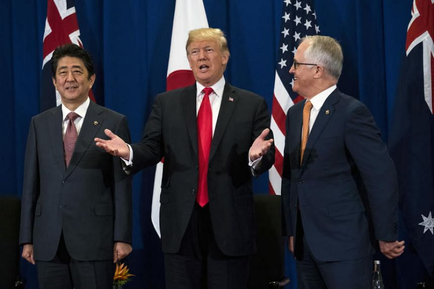 President Donald Trump is flanked by Prime Minister Shinzo Abe of Japan (left) and Prime Minister Malcolm Turnbull of Australia during the Association of Southeast Asian Nations summit meeting in Manila on Nov 13, 2017.