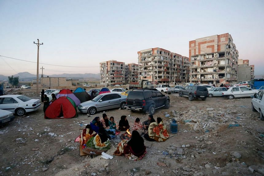 Residents huddle by a fire in an open area following the earthquake, at Sarpol-e Zahab in Iran's Kermanshah province on Nov 13, 2017.