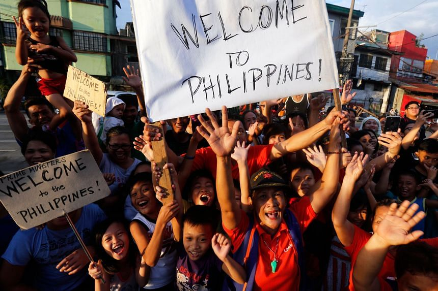 People greeting leaders arriving in Manila yesterday for a gala dinner to celebrate Asean's 50th anniversary, on the eve of the 31st Asean Summit. Earlier in the day, trade ministers from Asean countries and Hong Kong inked two free trade and inves