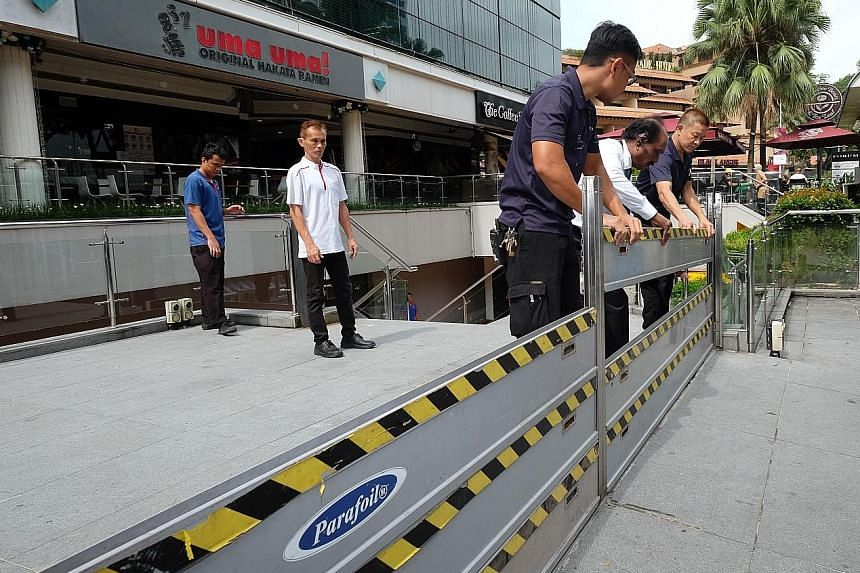 Workers from Forum The Shopping Mall in Orchard Road demonstrating how flood barriers are set up during the PUB briefing yesterday. They will be mobilised to set up the barricades should water activate flood sensors nearby.